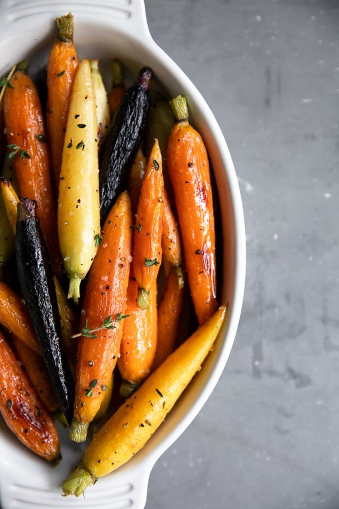 White serving dish filled with petit rainbow honey glazed carrots.