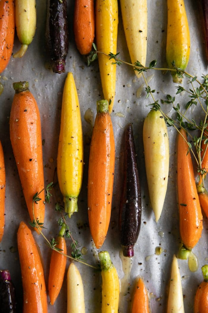 Petit Rainbow Carrots in rows on a baking sheet covered in ginger honey glazed and herbs.