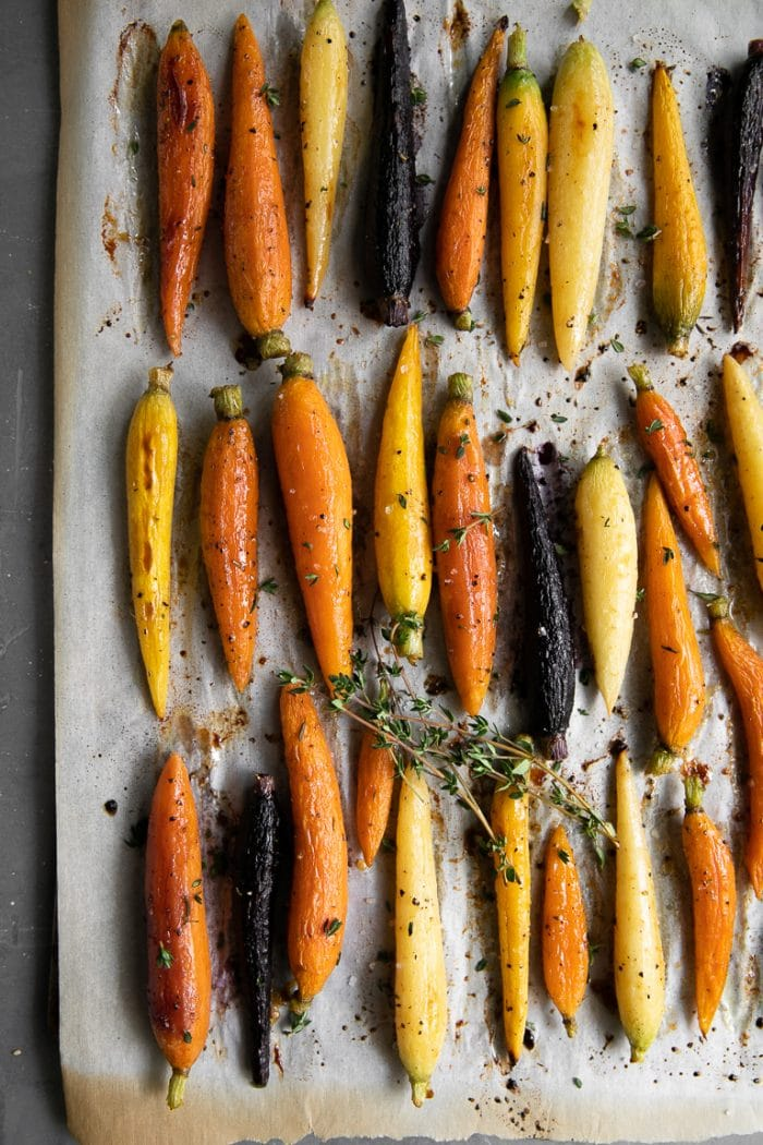 Fully cooked glazed rainbow carrots on a baking sheet.