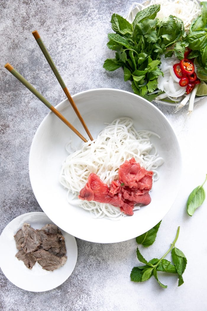 Large white soup bowl filled with rice noodles and thinly sliced beef tenderloin.