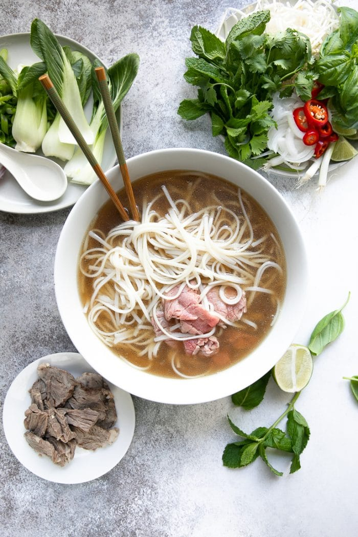 Large soup bowl filled with homemade pho broth, rice noodles, and thinly sliced tenderloin.