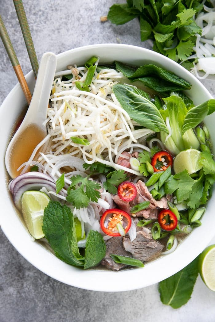 White bowl filled with pho broth, mung bean sprouts, fresh mint, thai basil, onions, and beef.