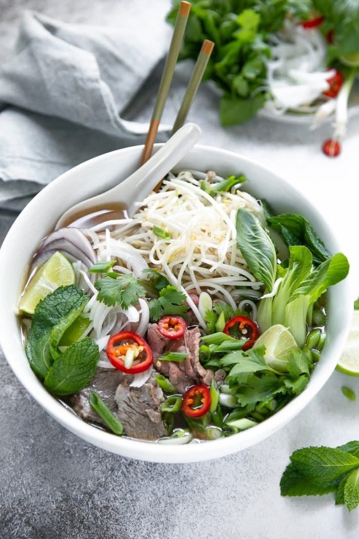 White bowl filled with homemade pho garnished with herbs, fresh greens, and filled with rice noodles.