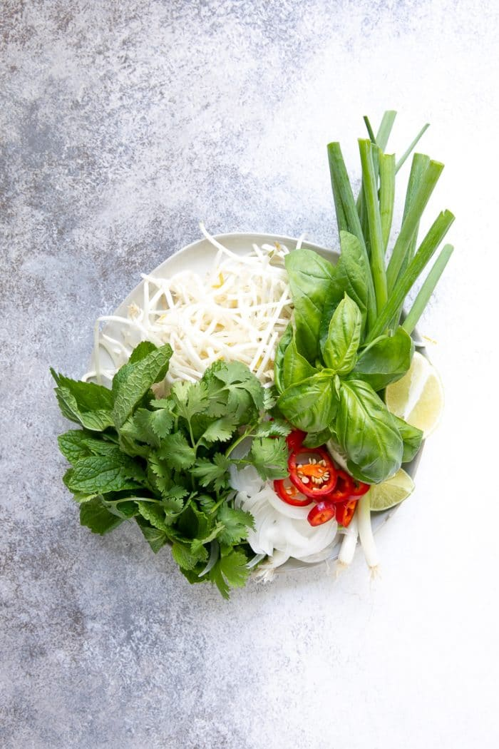 Plate with all the garnishes for pho (Vietnamese Noodle Soup) including green onions, limes, mung bean sprouts, mint, basil, and white onion.