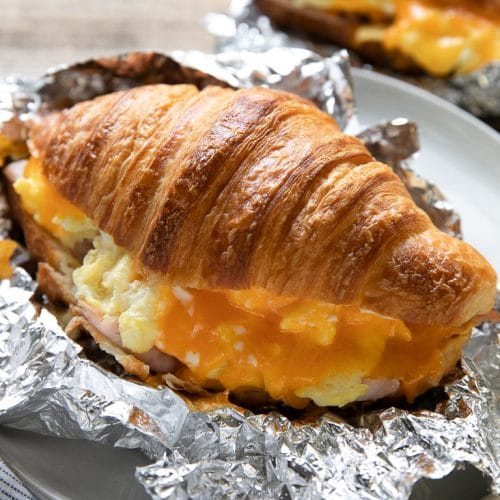 Large butter croissant filled with egg, ham, and melted cheddar cheese.