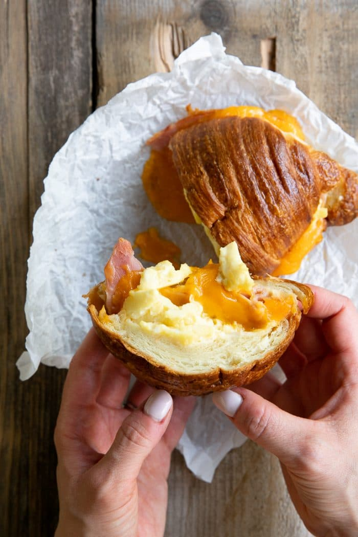Eating a croissant breakfast sandwich with ham, egg, and cheese.