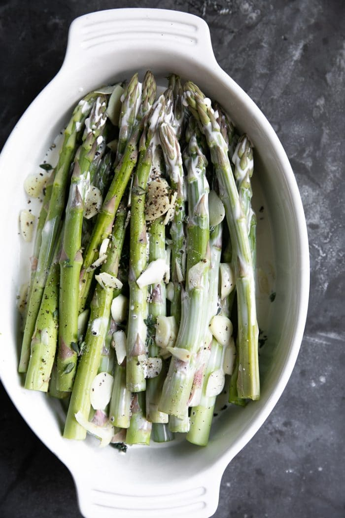 Raw asparagus,garlic, and cream in a white oval baking dish.