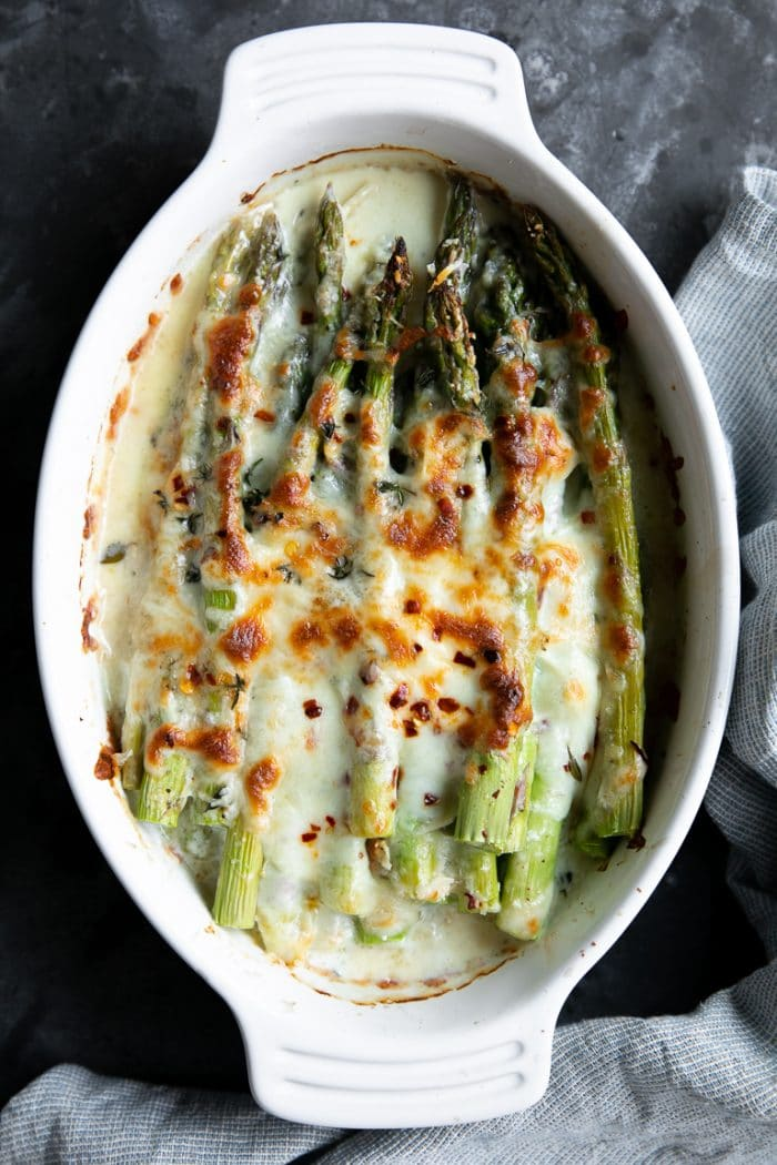 Cheesy Baked Asparagus Gratin in a white oval baking dish.