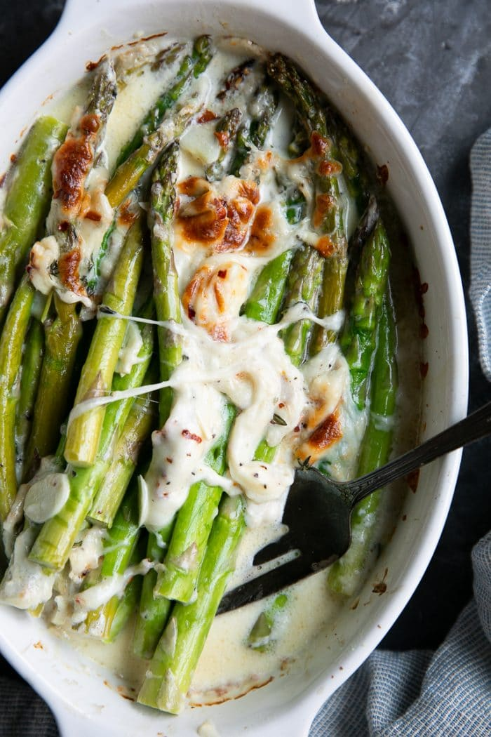 Baked asparagus in a white oval baking dish with melted cheese and garlic.