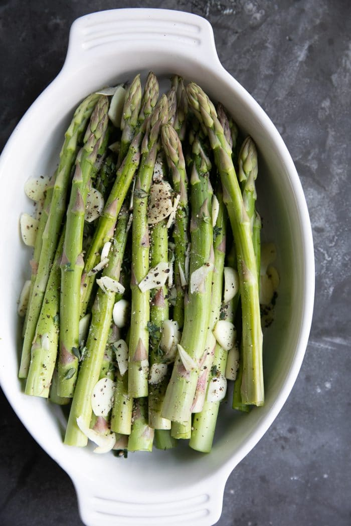 Raw asparagus and garlic in a white oval baking dish.