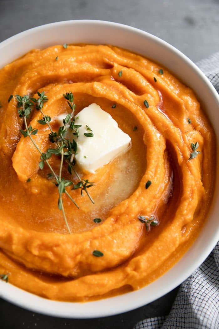 White bowl filled with creamy blended mashed sweet potatoes topped with butter and thyme.