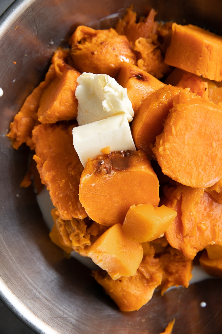 Mixing bowl filled with cooked sweet potato, steamed butternut squash, milk, and butter.