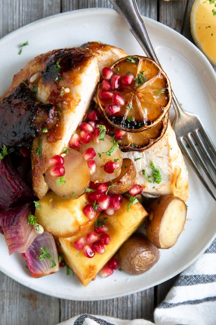 Plate served with harissa chicken, roasted red onion, acorn squash, red potatoes, and charred lemon slices, garnish with pomegranate arils and parsley.