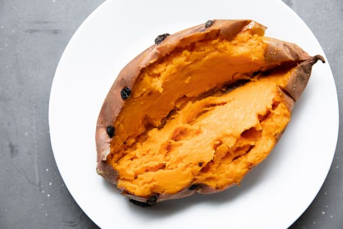 Ready to eat cooked sweet potato on a white plate.