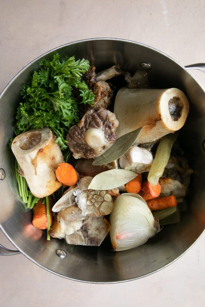 Roasted Bones with roasted veggies in a stock pot being made into bone broth