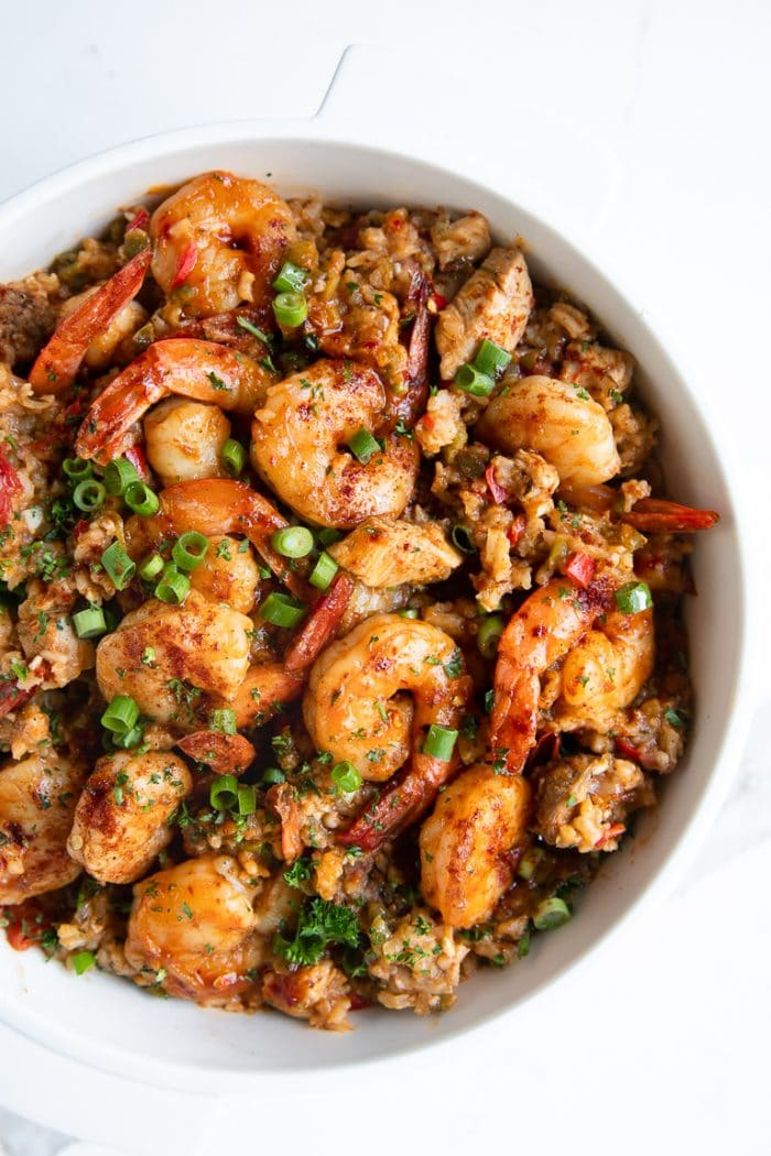 Large white pot filled with cooked jambalaya made with white rice, chicken, andouille sausage, and shrimp, and garnished with chopped parsley and green onions.