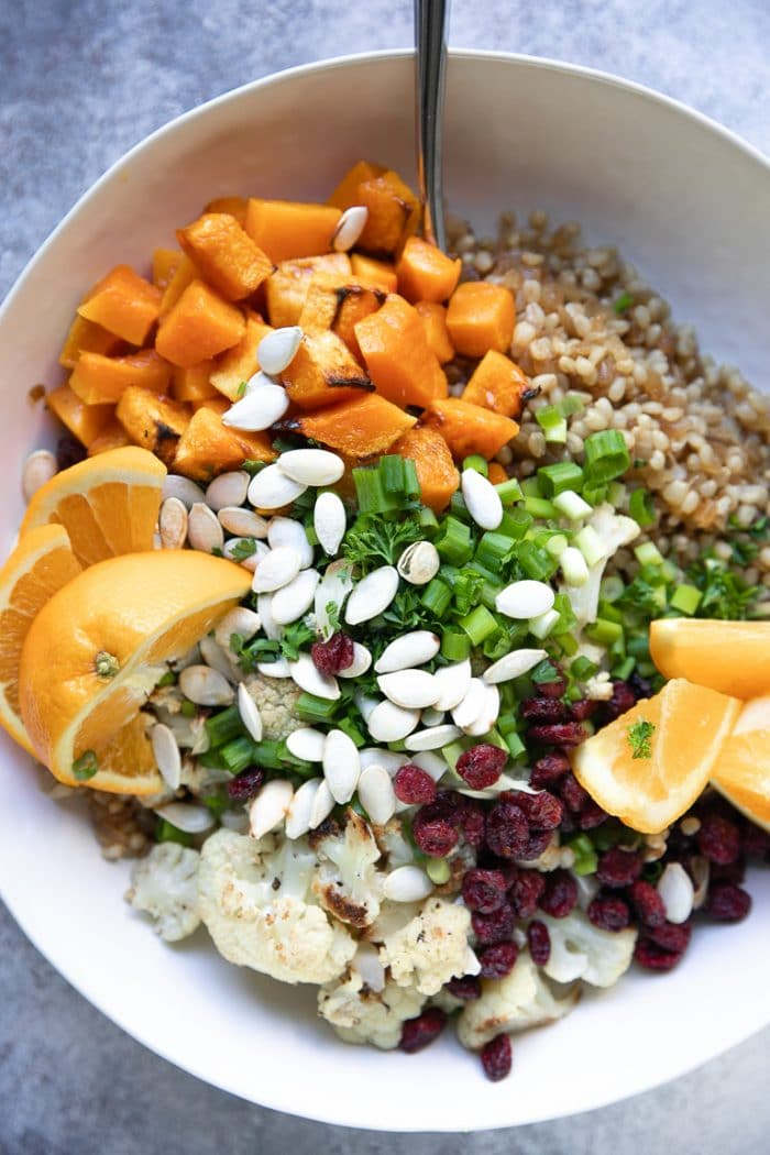 Salad bowl filled with cooked wheat berries, roasted butternut squash, cauliflower, dried cranberries, green onions, and pumpkin seeds.