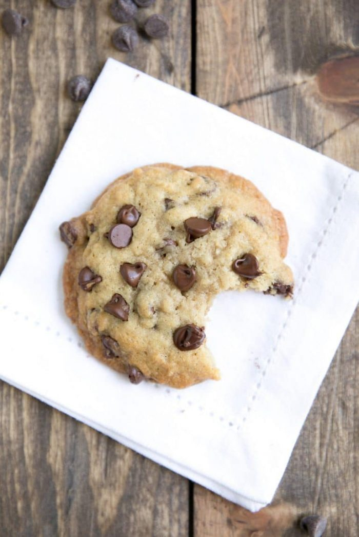 Large brown butter chocolate chip cookie on a white napkin with a bite taken from it.