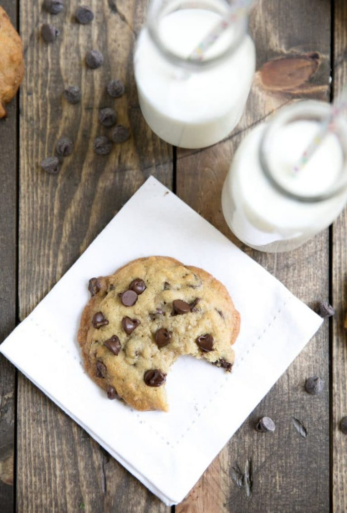 One chocolate chip cookie made with brown butter on a wood table set with milk.