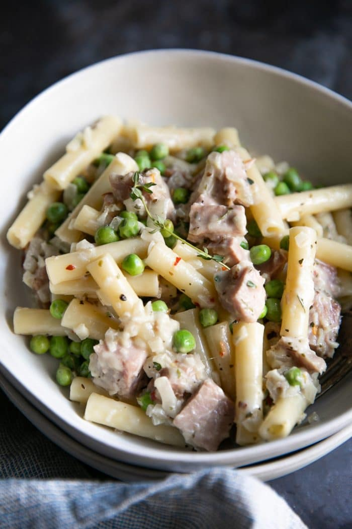 Creamy pasta in a while bowl filled with leftover ham, peas, and fresh thyme.