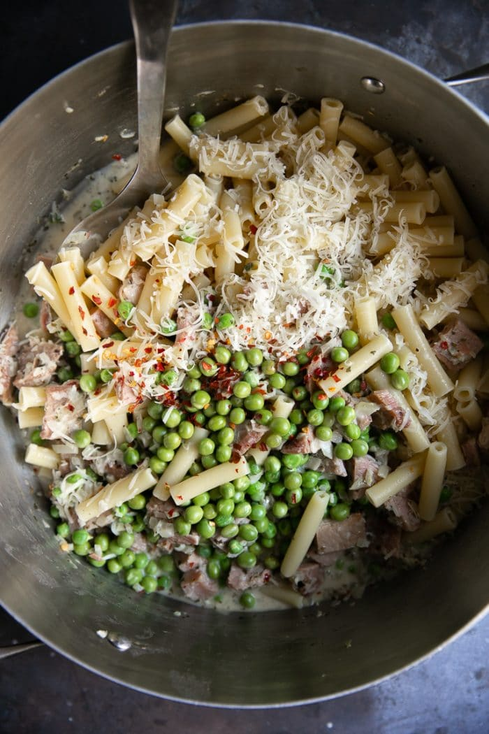 Large pot filled with cooked Ziti, a light parmesan cream sauce, peas, crushed red chili flakes, and leftover holiday ham.