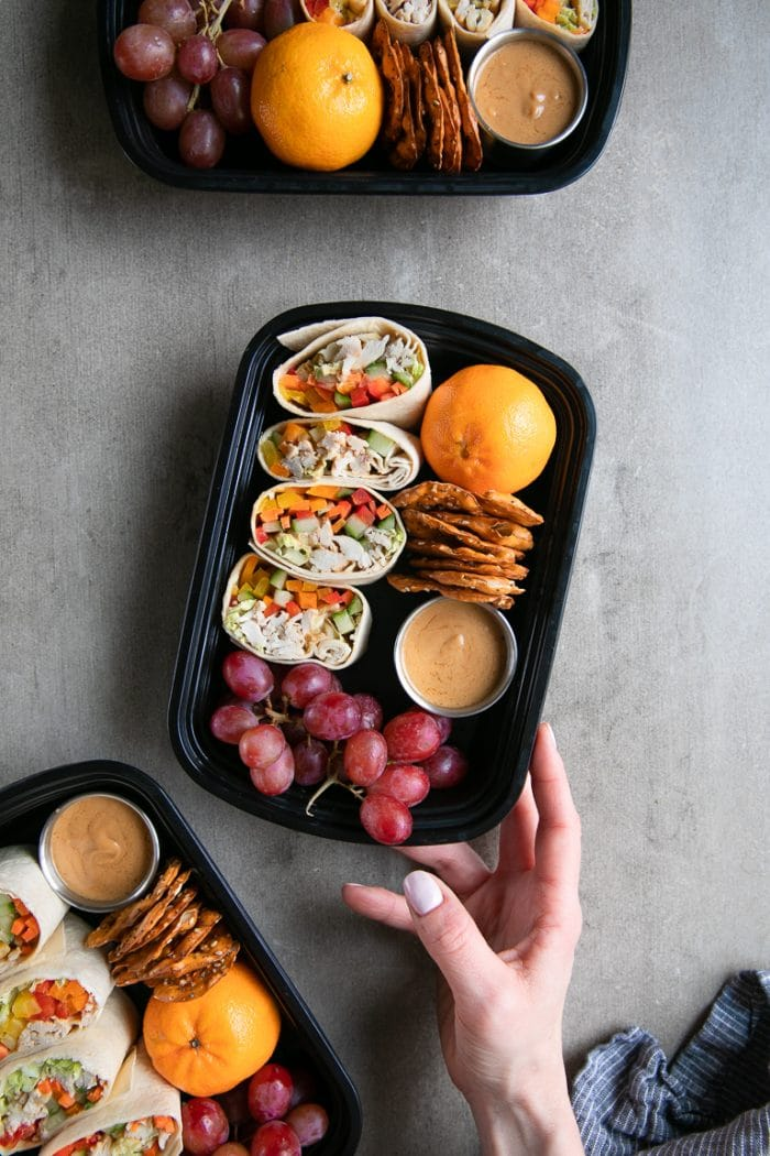 Thai chicken wrap meal prep trays filled with grapes, pretzels, and oranges.