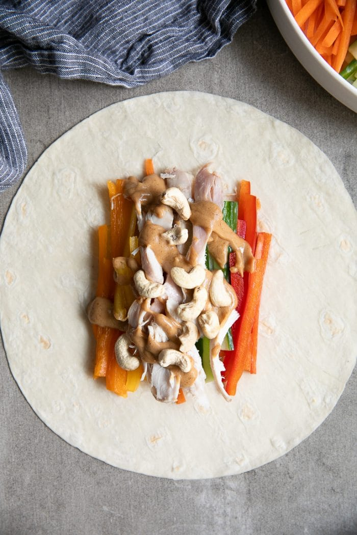 Low carb flour tortilla with sliced bell peppers, cucumber, chicken, cashews, and peanut sauce.