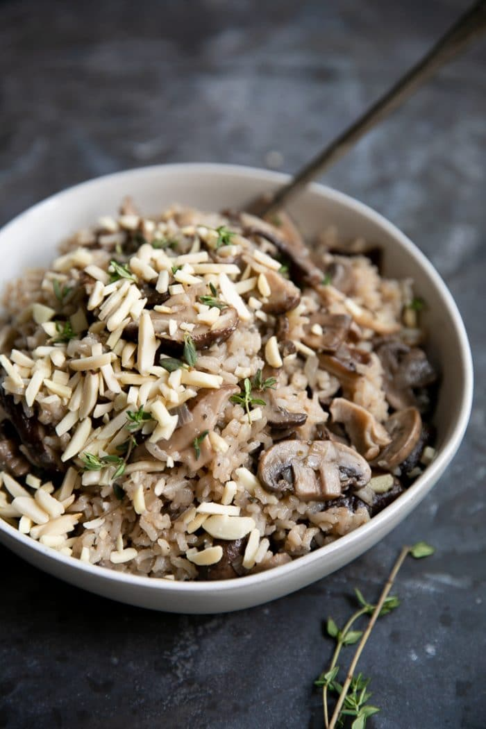 White bowl filled with RIce Pilaf with mushrooms and garnished with fresh thyme and slivered almonds.