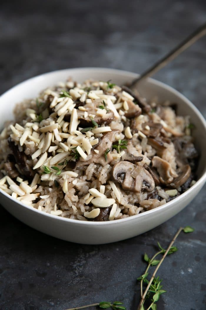 Cream-colored serving bowl filled with Mushroom Rice Pilaf and garnished with fresh thyme and slivered almonds.