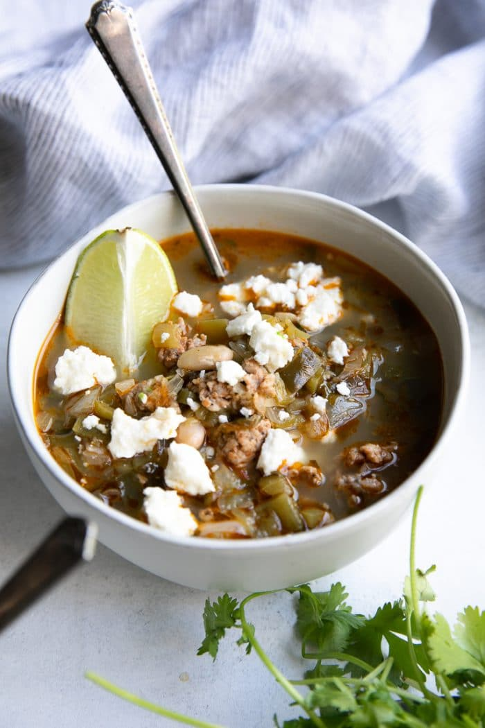 White bowl filled with Pork Green Chile with white beans and garnished with a lime wedge and cotija cheese.