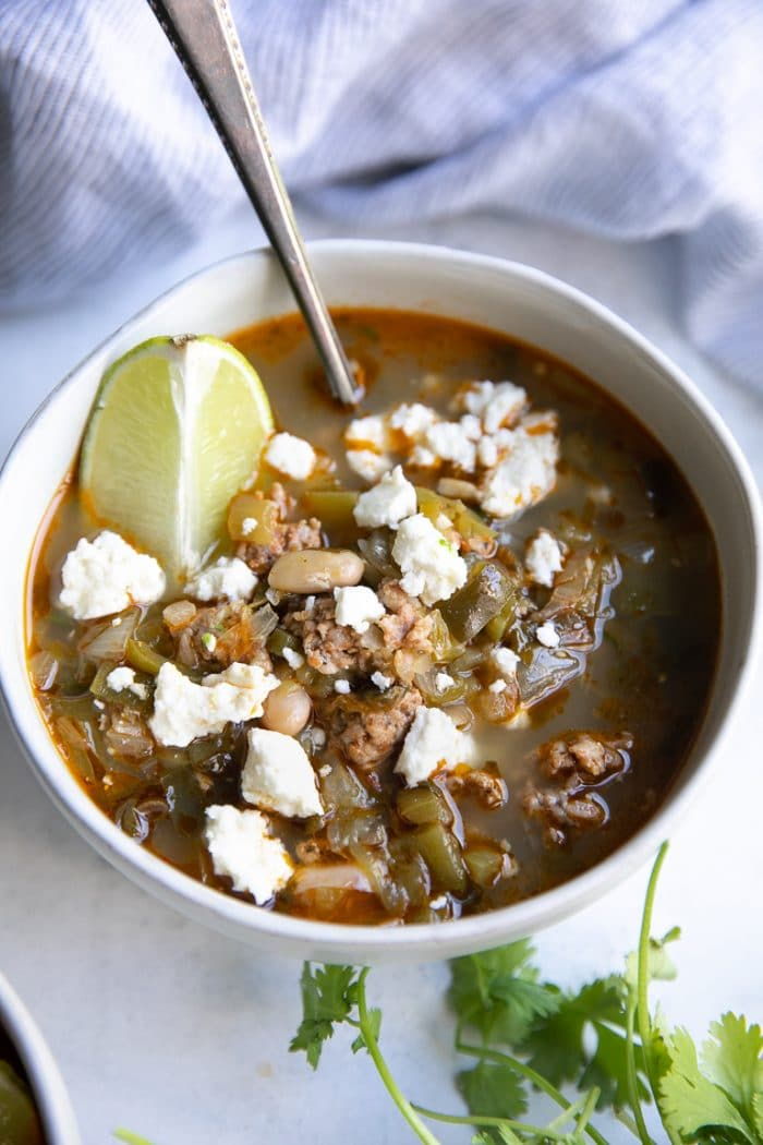 Close-up image of a white bowl filled with pork green chile made with ground pork, green chiles, onion, and garnished with lime and cotija cheese.