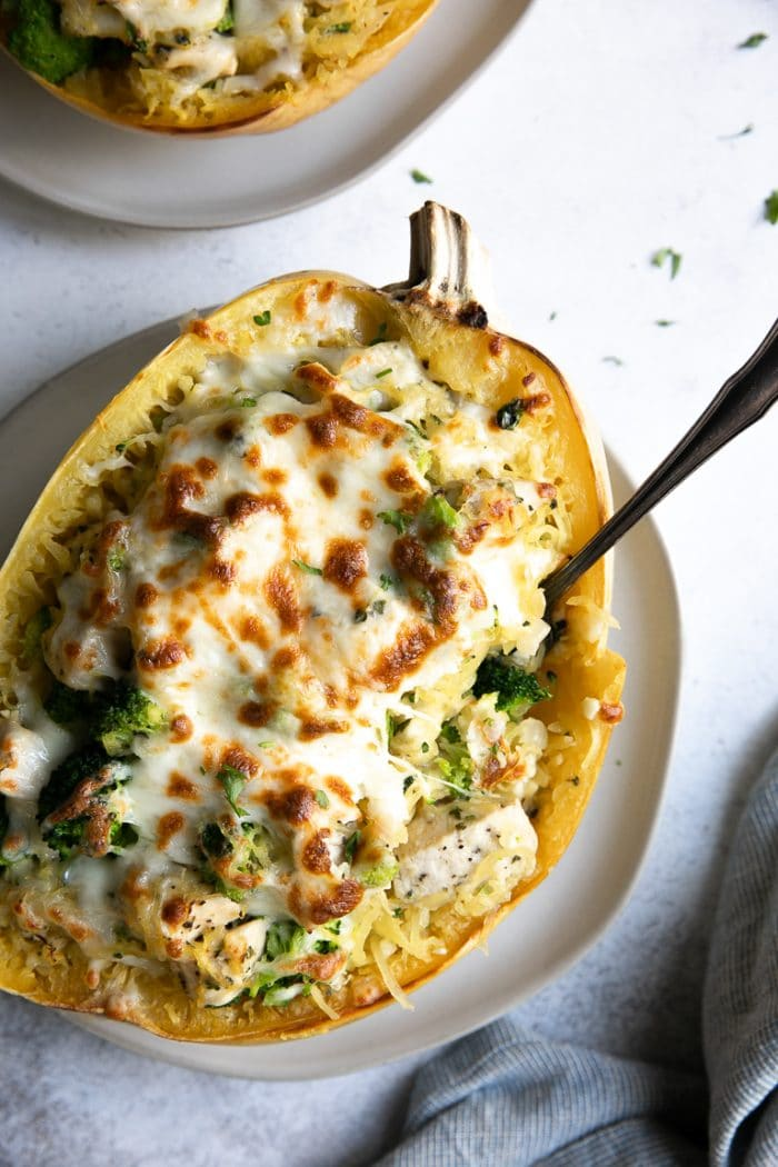 Stuffed spaghetti squash boat on a white plate filled with broccoli, chicken and cheese and topped with melted mozzarella cheese.