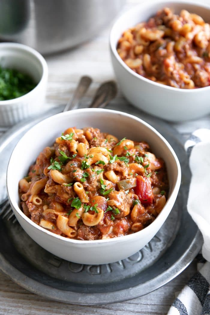 White bowl filled with American Goulash made with ground beef, tomatoes, and elbow macaroni.