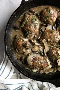 Salisbury steak meat patties with mushroom and onions in a rich gravy in a cast iron skillet.