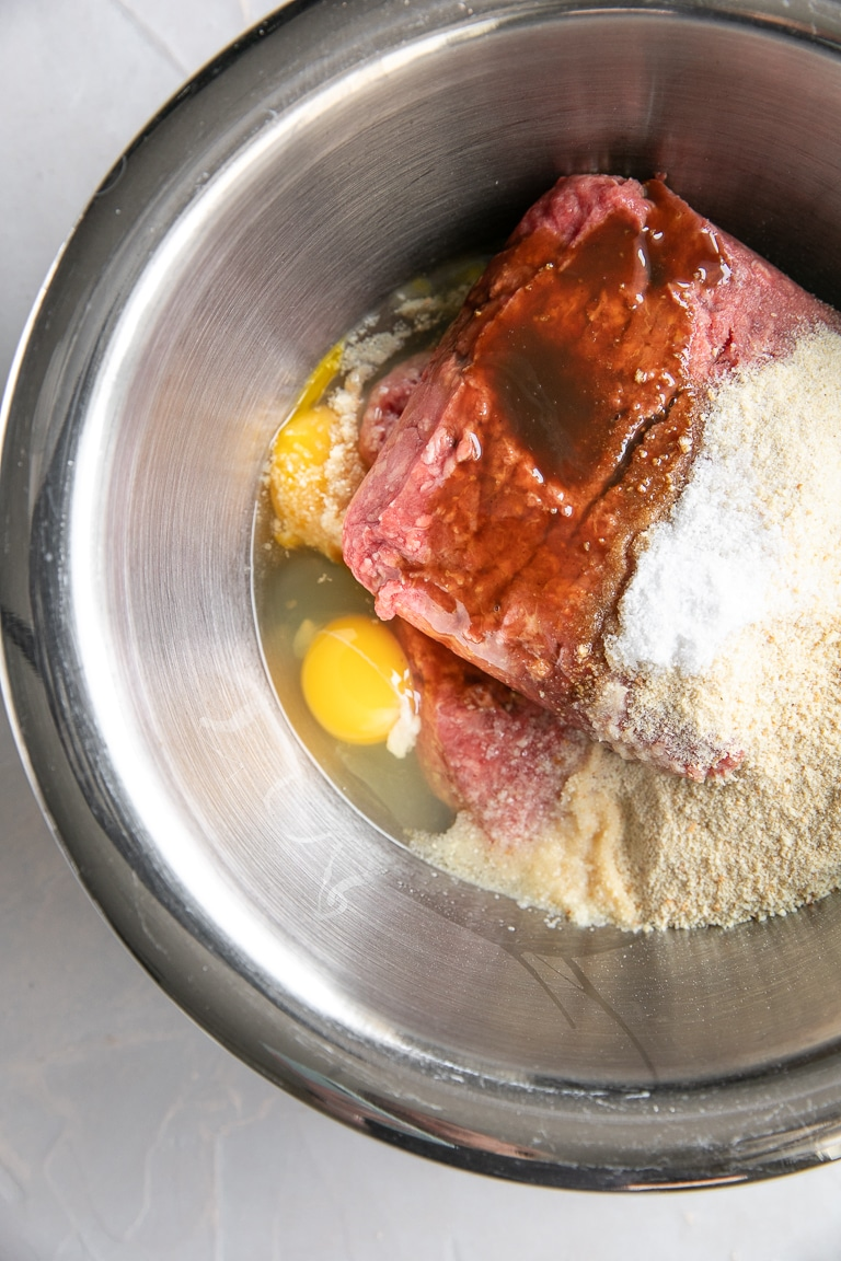 Large mixing bowl filled with ground beef, eggs, and breadcrumbs.