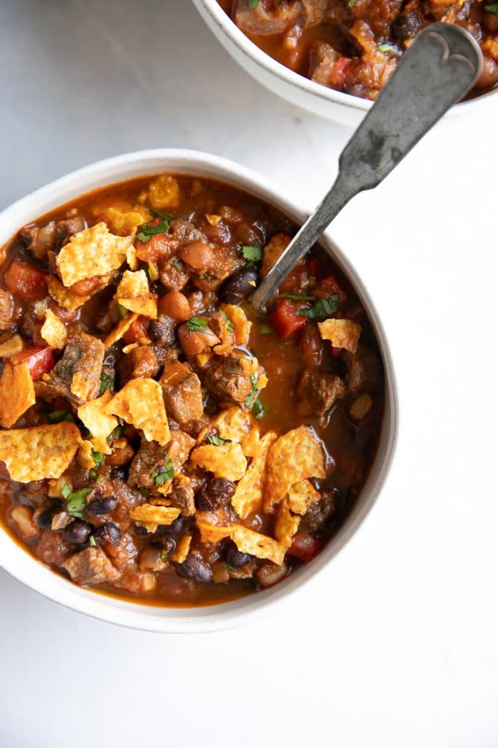 Overhead image of white bowl filled steak chili.