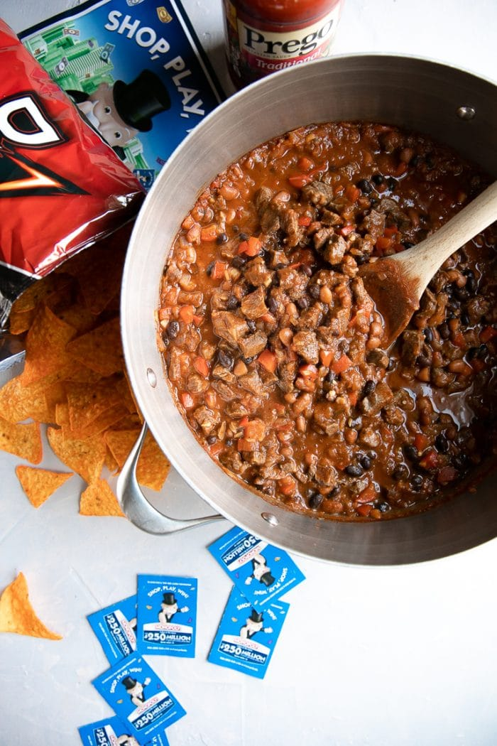 MONOPOLY Shop, Play, Win game board and game pieces with a large pot filled with steak chili.