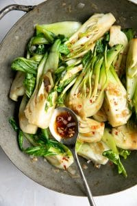 Bok Choy being cooked in a wok with a spoonful of garlic sauce