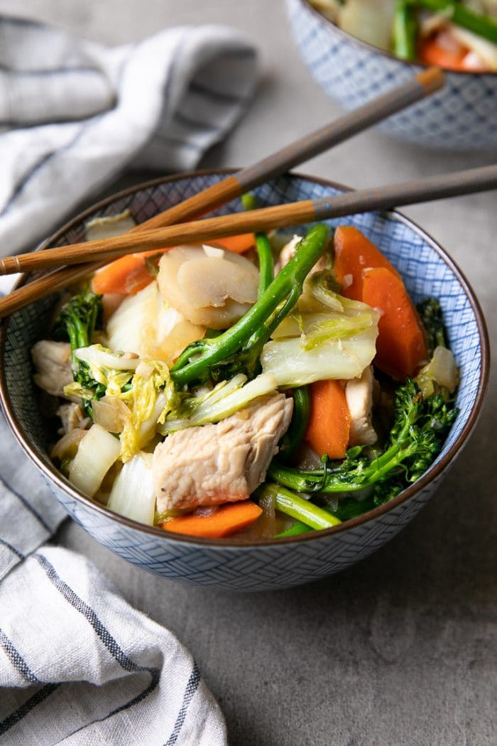 Blue and white bowl filled with chicken, cabbage, broccoli stir fry with chopsticks resting on top.