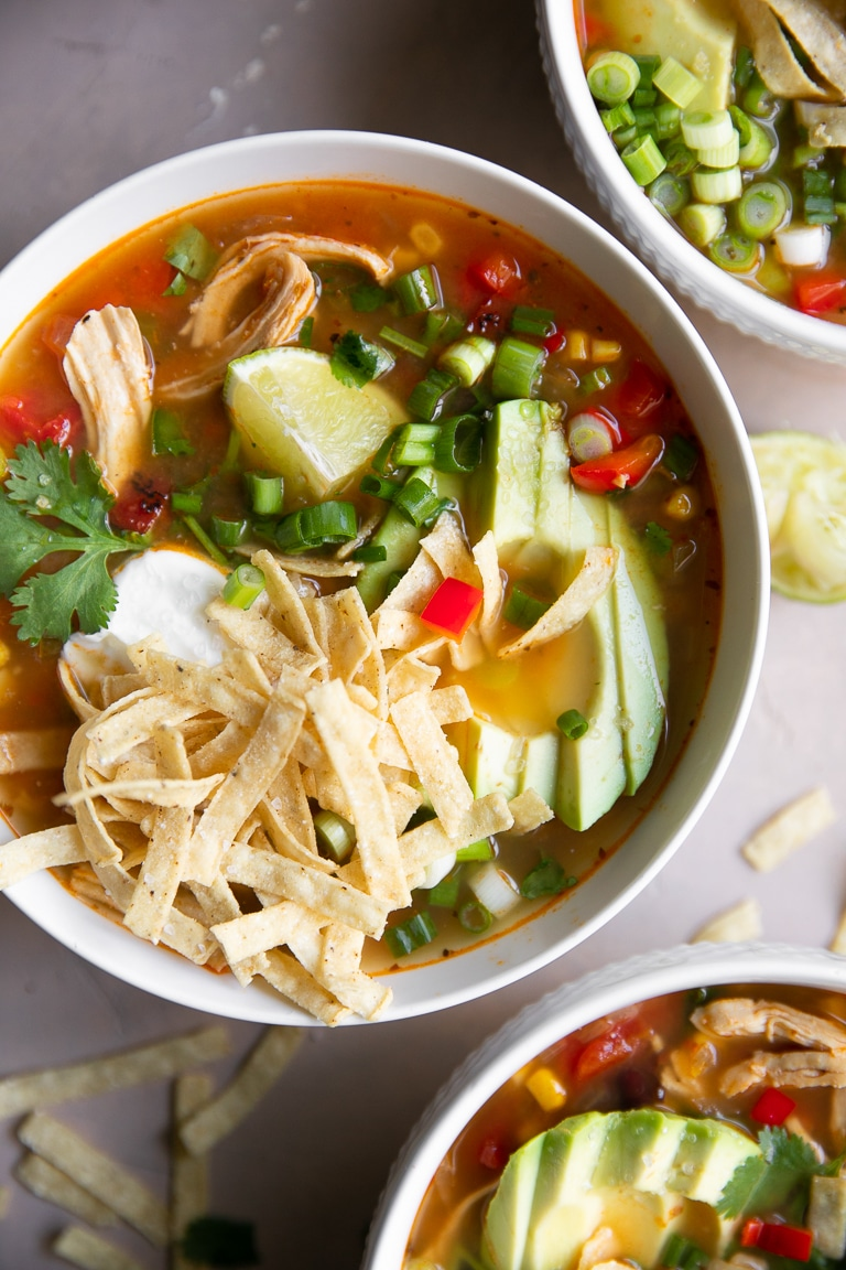 White bowls filled with chicken tortilla soup and topped with avocado, sour cream, and tortilla strips.