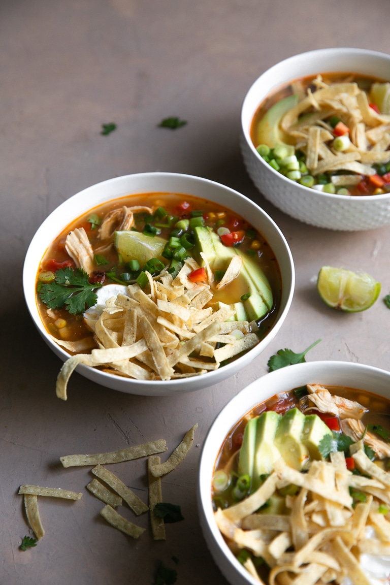 White bowls filled with chicken tortilla soup and garnished with tortilla strips, avocado, and green onions.