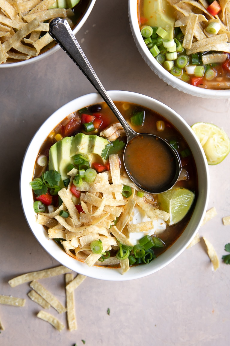 Bowl filled with chicken tortilla soup and spoon filled with soup broth.