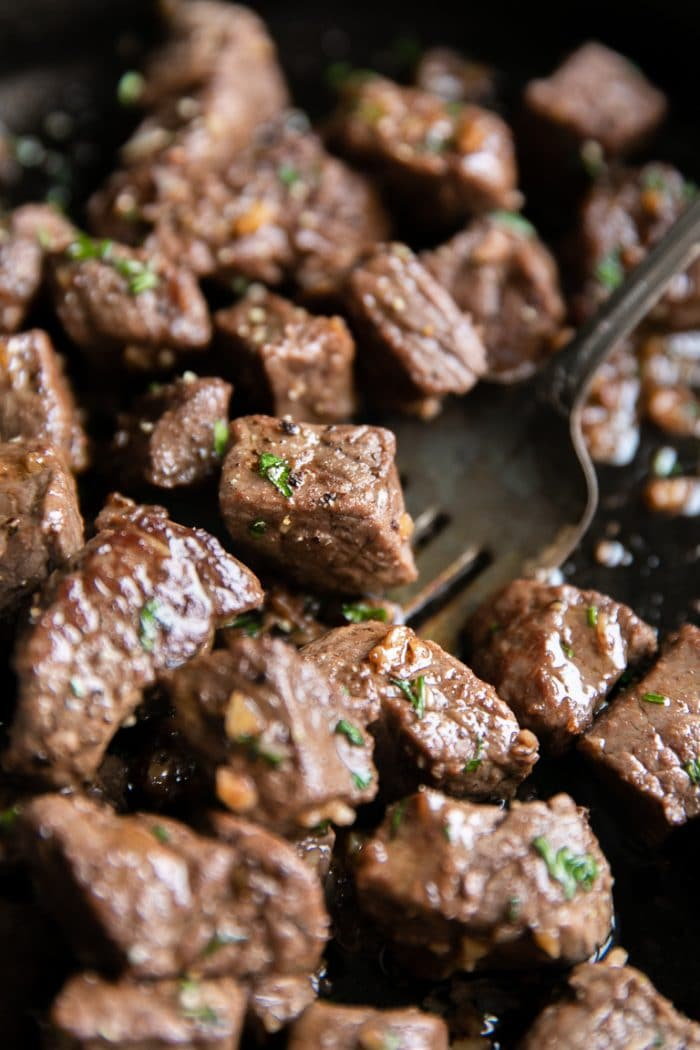 Close up image of cut-up sirloin steak bites cooked in a garlic butter sauce.