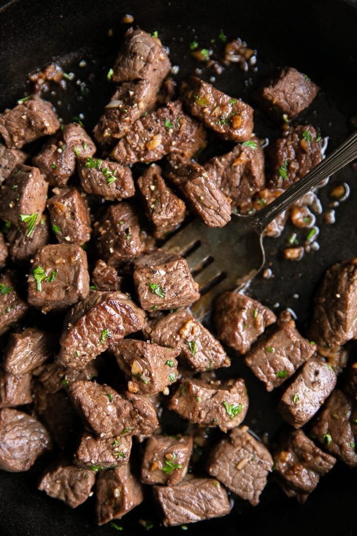 Cooked garlic butter steak bites in a cast iron skillet.