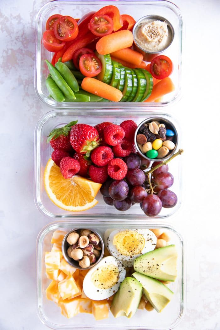 Three glass meal prep containers filled with raw vegetables, mixed fruits, and different proteins such as egg, cheese, and avocado.