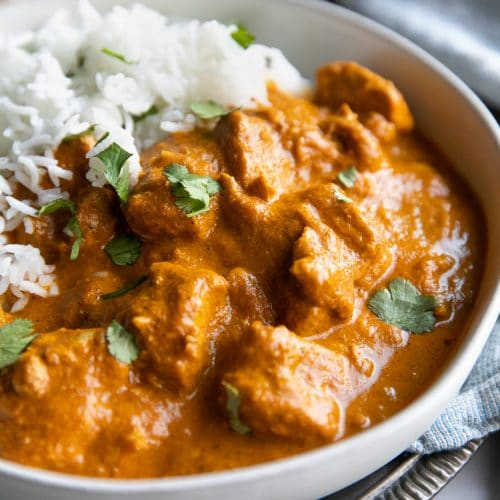 White serving bowl filled with chicken tikka masala and basmati rice garnished with fresh cilantro.