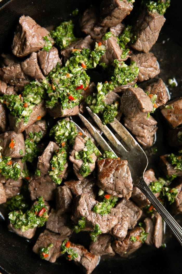 Close-up image of Steak Bites drizzled with homemade Chimichurri in a large Cast Iron skillet.