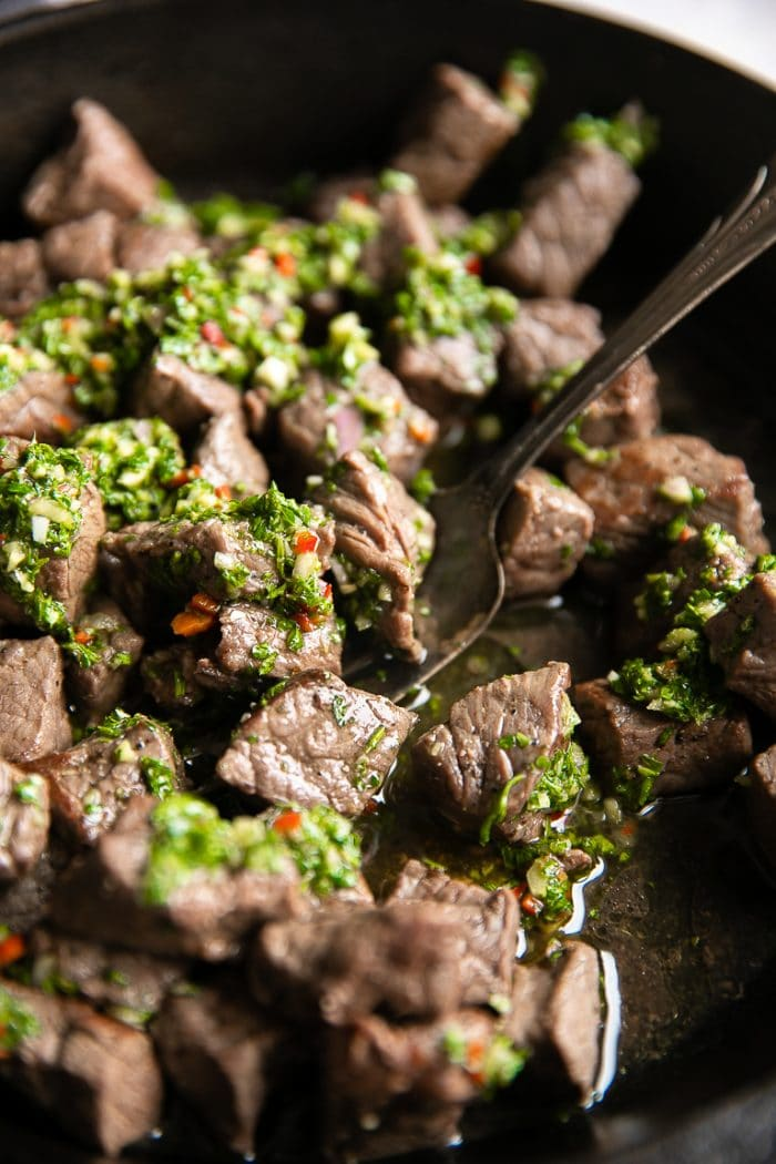 Large silver fork scooping up steak bites covered with chimichurri sauce from a black cast iron skillet.