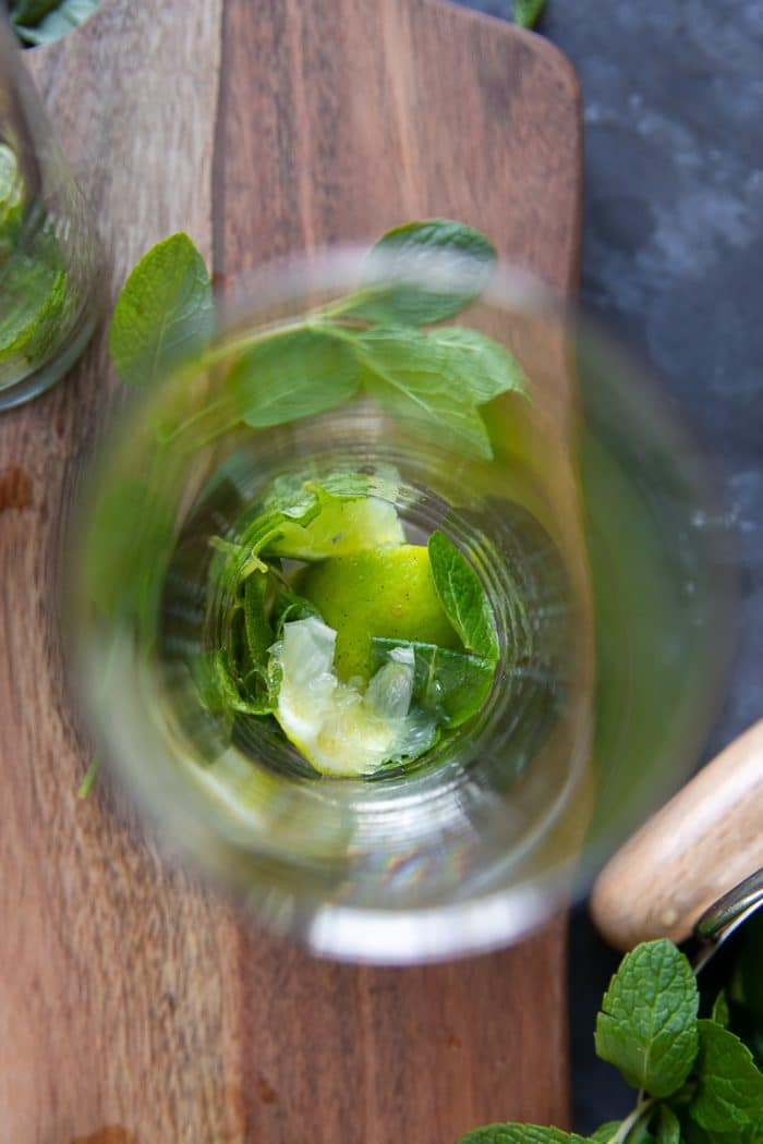 Overhead image of a highball glass with muddled lime and fresh mint.