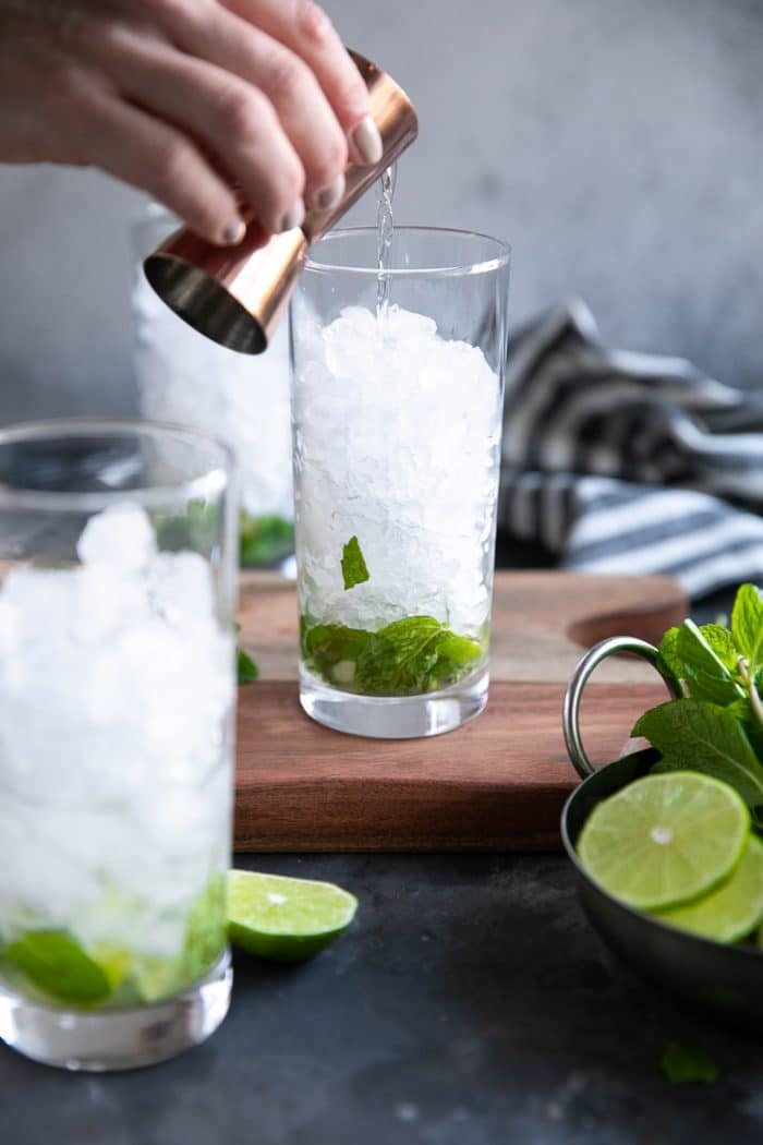 White rum being poured into a highball glass filled with muddled lime, mint and filled with crushed ice.